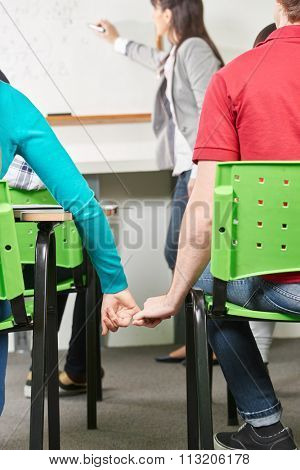 Two teenagers in love hold hands in class