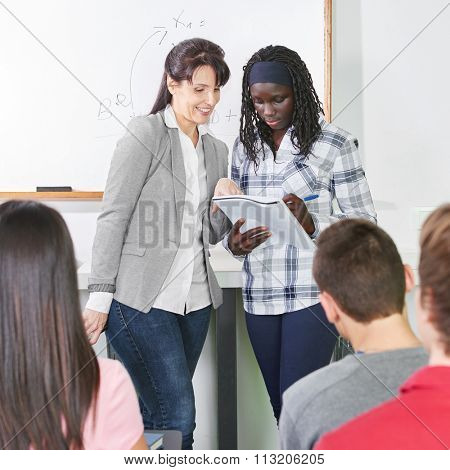 Teacher helps her african student with ther presentation