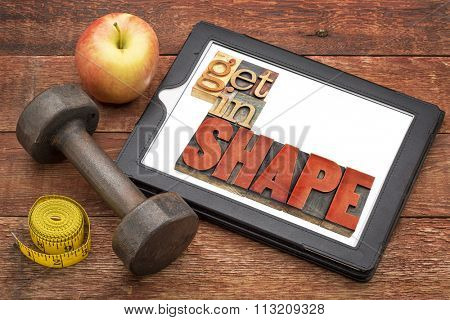get in shape motivation fitness concept - text  in vintage letterpress wood type on a digital tablet, with a dumbbell, apple and tape measure