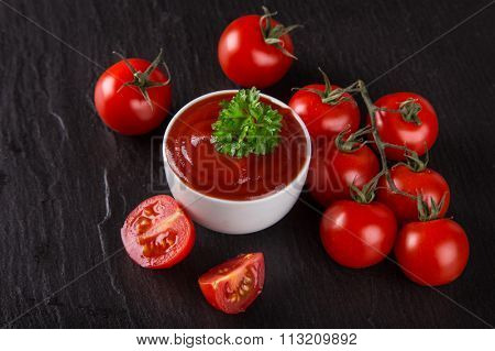 Bowl of tomato sauce and cherry tomatoes on stone table.