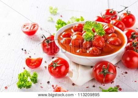 Bowl of tomato sauce and cherry tomatoes on wooden table.