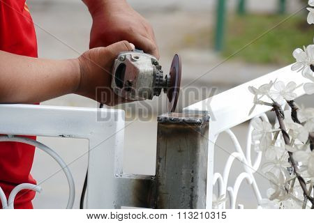 The Worker Use Metal Grinding Wheel To Grind The Iron Pole