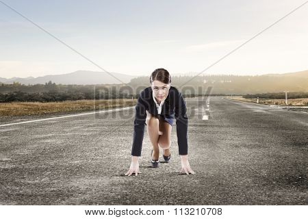Young determined businesswoman standing in start position ready to compete