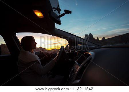 Woman in the car enjoying sunset