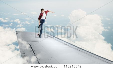 Skater boy doing stunt on edge of flying airplane