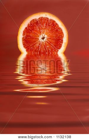 Juicy Half Of A Blood Orange In Water On A Red Background