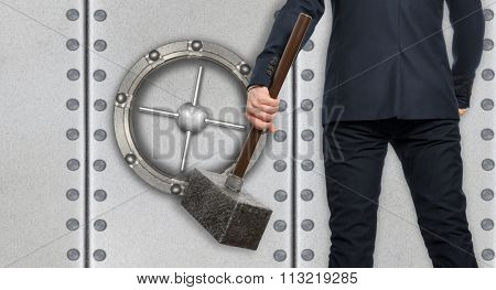 Determined businessman with hammer in hands on the background safe