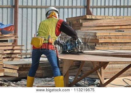 Carpenter using circular saw at the construction site