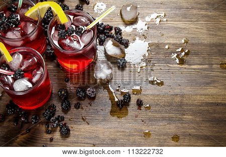 Making Cocktail Of Berries , Ice And Lemon On Wooden Background.