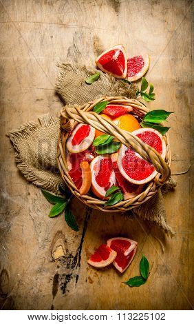 Grapefruit Background. Grapefruit Sliced In The Old Basket With Leaves.