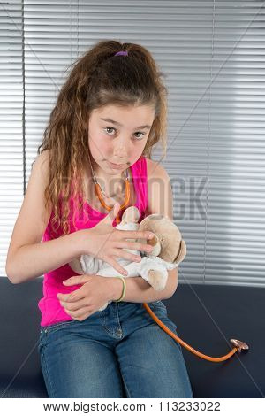 Beautiful Little Girl Pretending To Be A Nurse And Auscultate Her Teddy-bear