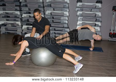 Portrait Of A  Woman Balancing On The Ball At Fitness Center