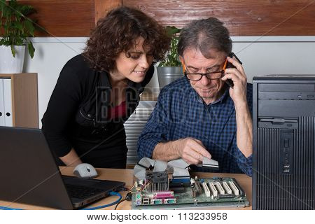 Man Fixing A Computer In Front Of His Customer At Office