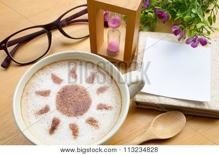 latte art coffee in sun design with papernote and sandglass on wooden vintage table