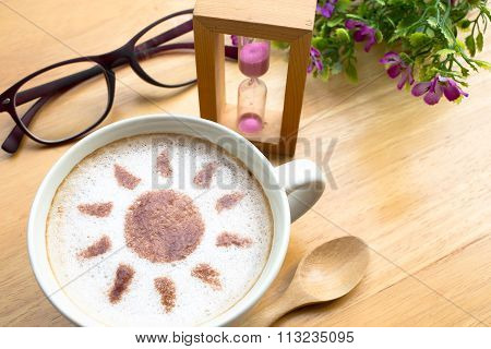 latte art coffee in sun design with sandglass and eyeglasses on wooden vintage table