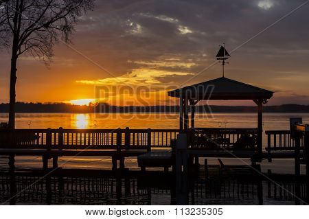 A colorful sunset over water with a pier in the foreground