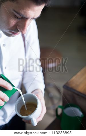 Barista Pouring Froth Milk In Coffee