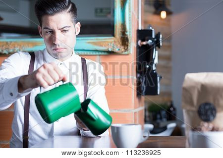 Barista Pouring Milk From One Pitcher To Another