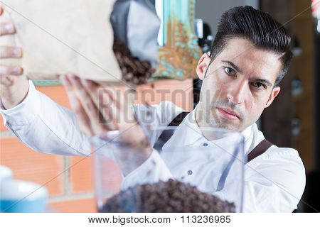 Bartender Filling Up Coffee Beans And Looking At Camera