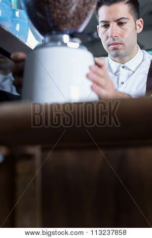 Male Bartender Grinding Coffee Beans