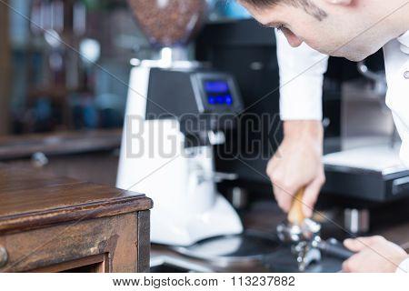 Male Bartender Pressing Coffee In Holder