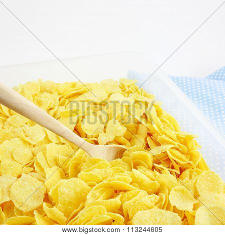 The tasty golden corn flakes and wooden spoon in plastic container box