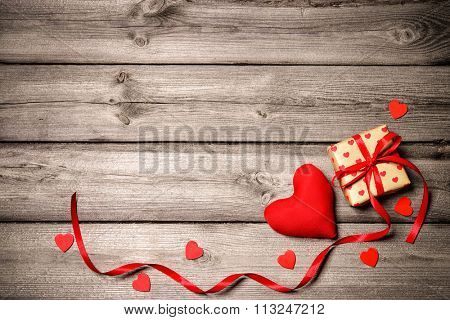 Valentines day vintage background with hearts and a gift box on wooden board
