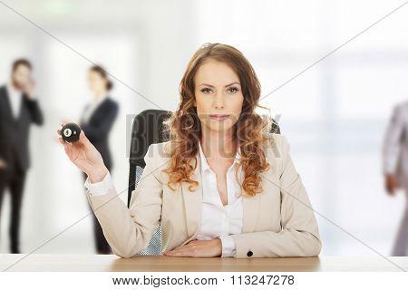 Businesswoman holding eight billiard ball by a desk.