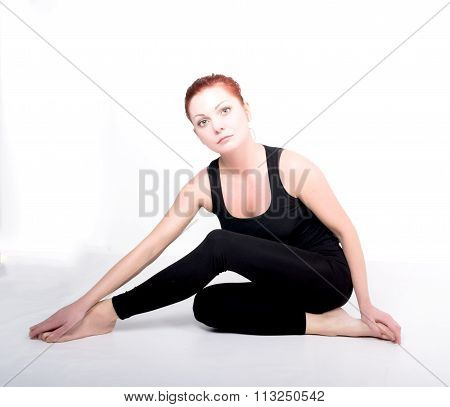 beautiful slim girl in sportswear is engaged in sports. She bent her knees doing exercises yoga