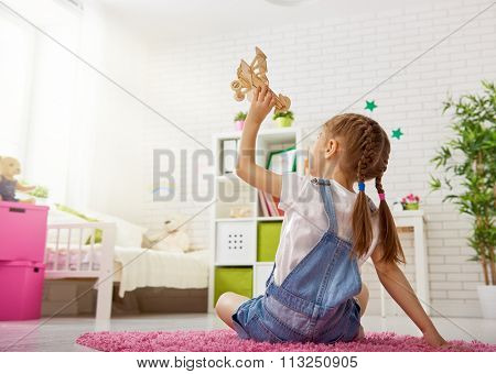 happy child girl. little girl playing with toy airplane at home. leisure and play in the nursery