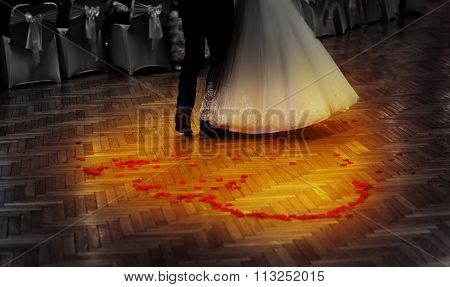 bride and groom dancing on a wedding dancefloor with rose petals in heart shape.