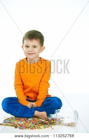 Kid sitting cross-legged on floor with sweets jar spilled. Happy, looking at camera, isolated on white.
