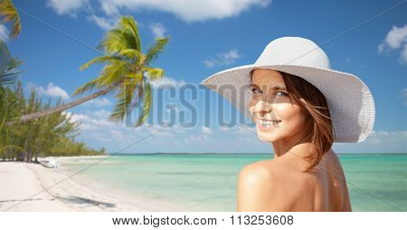 happy young woman in sunhat over summer beach