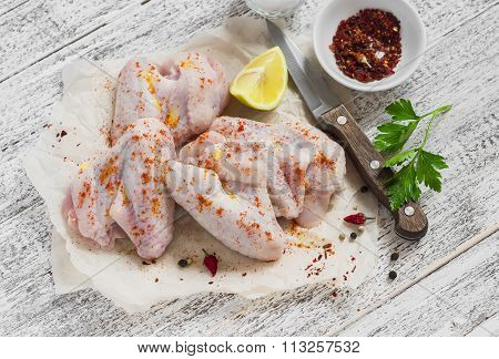 Raw Ingredients To Prepare Spicy Chicken Wings, Spices, Salt, Parsley, Chicken Wings On A Light Wood