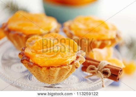 Sweet cakes with tangerines on plate, close up