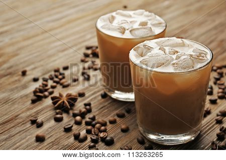 Two cups of ice coffee with coffee beans on wooden table