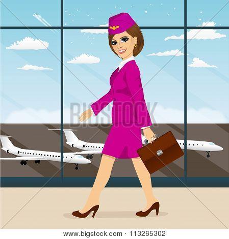 stewardess with briefcase walking through airport terminal