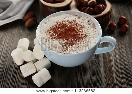 Cup of hot cacao with marshmallow on wooden background, close up