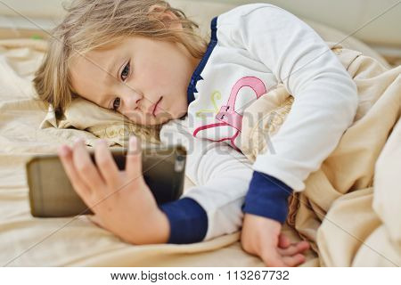 Little Girl  In Bed With Smartphone