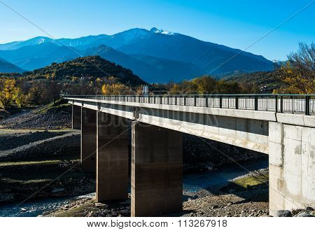 Bridge across the river in the French Pyrenees and picturesque mountain range