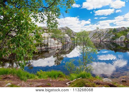 Clouds Are Reflected In The Small Lake Among Huge Stones In The Mountains Of Norway
