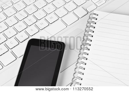 Closeup high angle view of a laptop computer with a cell phone and note pad laying across the keyboard