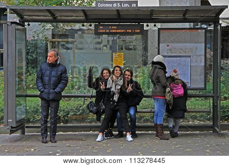 people are waiting for bus on stop station in Milan