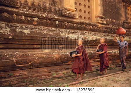 Southeast Asian young Buddhist novice monks walking morning alms in Old Bagan, Myanmar