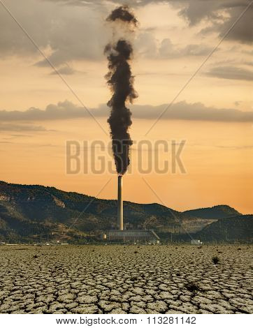 Thermal plant with black fume and the cracked dry land on the foreground