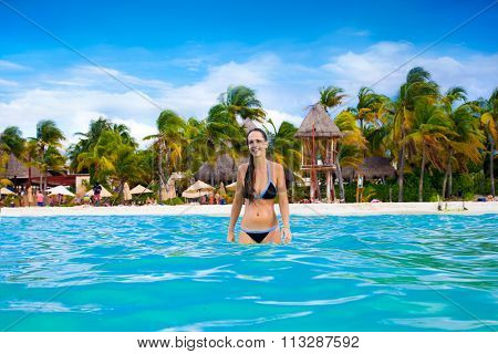 Beautiful blissful woman in bikini enjoying tropical Norten beach on colorful Isla Mujeres island near Cancun in Mexico. Latin America.