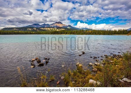 Magic lake Annette in reserve surrounded by pine forests. Canadian Rocky Mountains, lake Annette, Jasper National Park