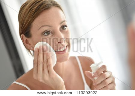 Woman in bathroom cleansing face in front of mirror