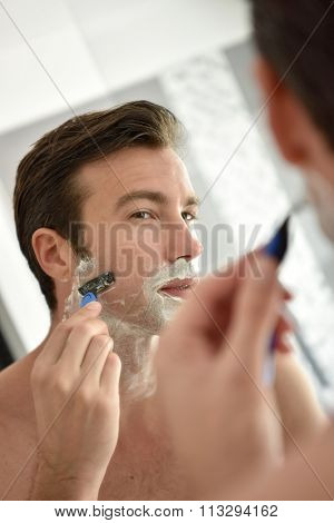 Adult man shaving with foam and manual razer