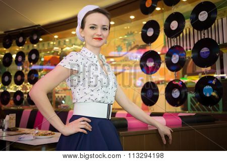 Young woman in retro dress in bar decorated phonograph records